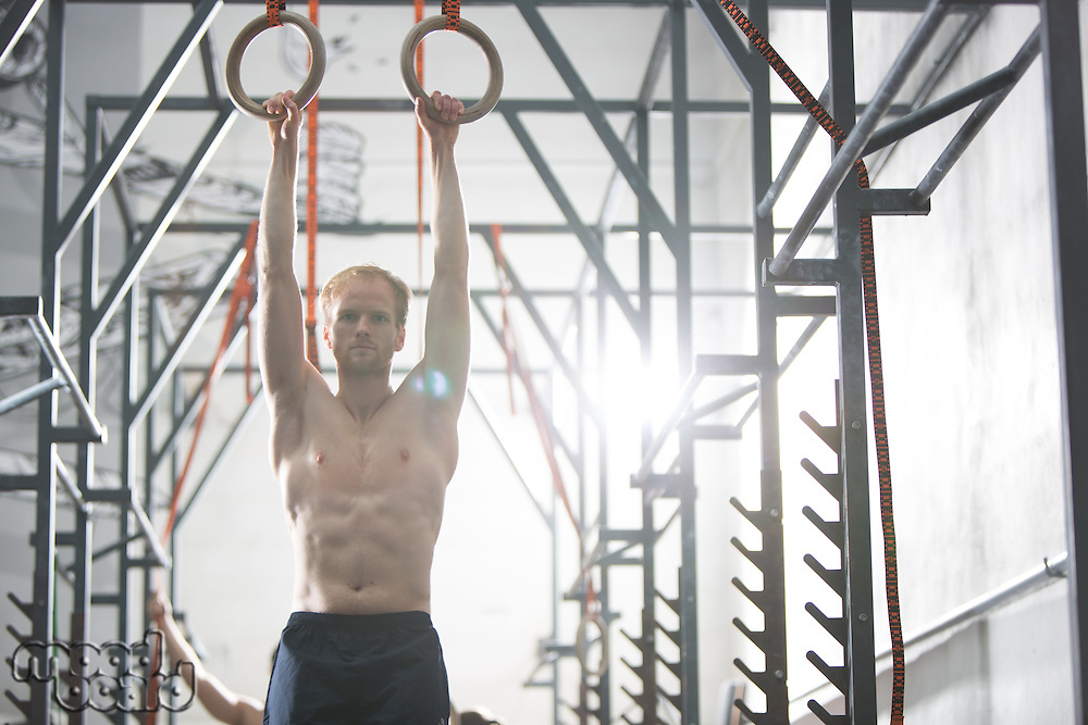 Confident man exercising with gymnastic rings in crossfit gym
