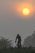 UNITED KINGDOM, London: 18 April 2019 <br /> A cyclist makes his way through Richmond Park as the sun rises behind him on what is set to be a warm April's day. Temperatures for the Easter weekend are set to reach 25C.<br /> Rick Findler / Story Picture Agency