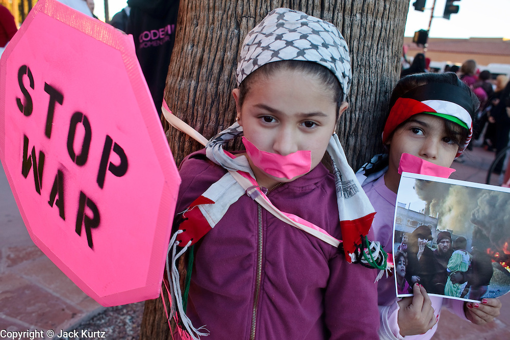 30 DECEMBER 2008 -- PHOENIX, AZ: NARMEEN GHAZQWNEH, 8, left, and IBTESAL ALI, 6, tied themselves to a tree in Phoenix, AZ, Tuesday, to protest Israeli attacks on Gaza. About 200 people from a variety of human rights and peace activists organizations in Phoenix, AZ, marched in opposition to the Israeli attacks on Gaza and in favor of Palestinian rights on Tuesday, the fourth day of Israeli air strikes on Hamas facilities in Gaza. Photo by Jack Kurtz / ZUMA Press