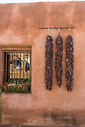 Dried chile pepper ristras hang on an adobe wall in the Old Town Plaza December 14, 2015 in Albuquerque, New Mexico.