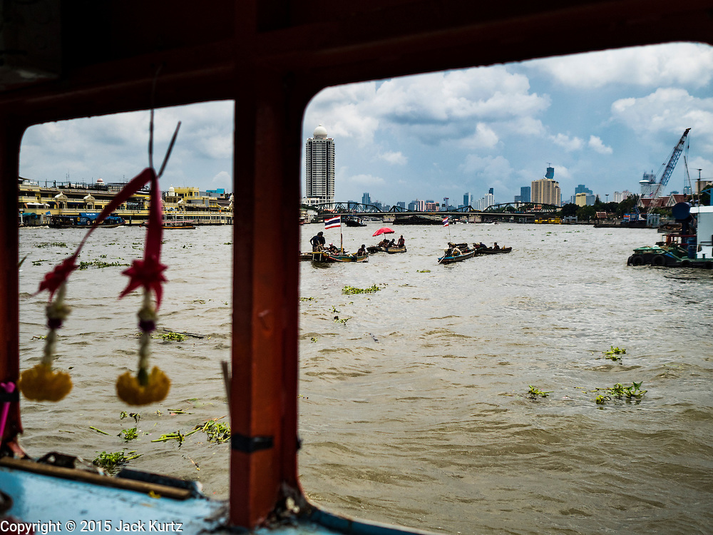 06 OCTOBER 2015 - BANGKOK, THAILAND:  Salvage divers, seen through the window of a pedestrian ferry, work the Chao Phraya River in Bangkok. Divers work in two man teams on small boats in the Chao Phraya River. One person stays in the boat while the diver scours the river bottom for anything that can be salvaged and resold. The divers usually work close to shore because the center of the river is a busy commercial waterway with passenger boats and commercial freight barges passing up and down the river all day long. The Chao Phraya is a dangerous river to dive in. It's deep, has large tidal fluctuations, is fast flowing and badly polluted. The divers make money only when they sell something.    PHOTO BY JACK KURTZ