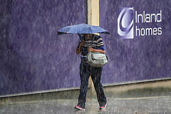 © Licensed to London News Pictures. 10/08/2018. London, UK. A woman shelters under an umbrella as a sudden rain shower hits Uxbridge. Photo credit: Peter Macdiarmid/LNP