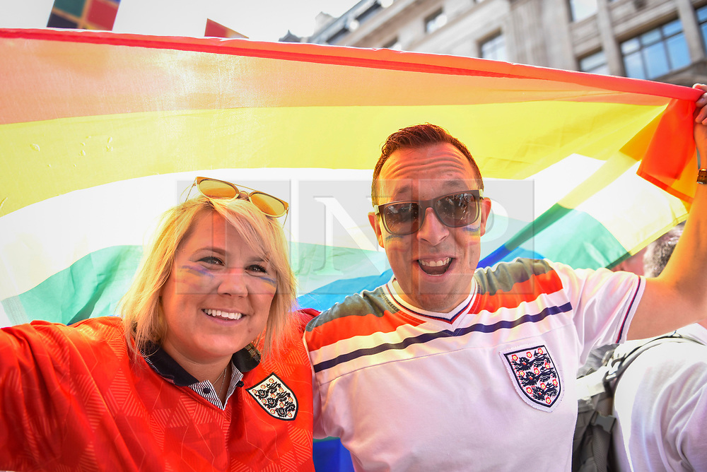 © Licensed to London News Pictures. 07/07/2018. LONDON, UK. England fans, en route to the Olympic Park to watch the England v Sweden World Cup football match, view the annual Pride in London Parade, the largest celebration of the LGBT+ community in the UK.  Photo credit: Stephen Chung/LNP