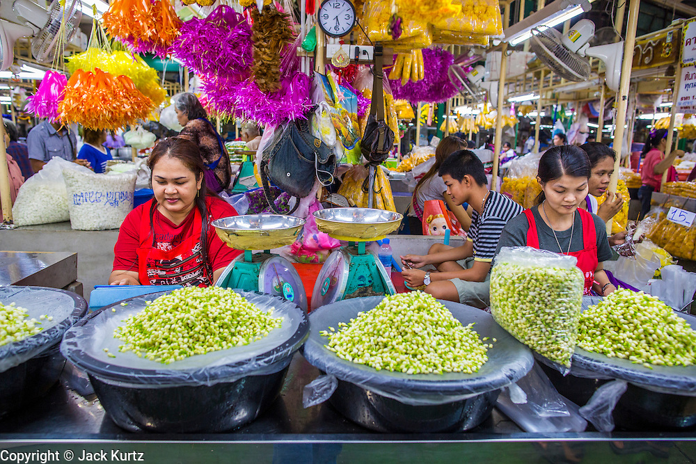 19 OCTOBER 2012 - BANGKOK, THAILAND:   Workers make garlands in the Bangkok Flower Market. The Bangkok Flower Market (Pak Klong Talad) is the biggest wholesale and retail fresh flower market in Bangkok.  The market is busiest between 3:30AM and 6AM. Thais grow and use a lot of flowers. Some, like marigolds and lotus, are used for religious purposes. Others are purely ornamental.       PHOTO BY JACK KURTZ