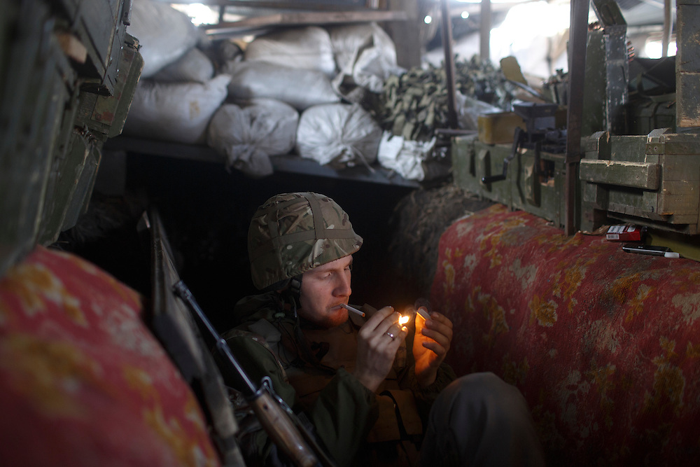 A volunteer with Dnipro-1 battalion lights a cigarette in the trenches on the front on March 20, 2015 in Pisky, Ukraine.