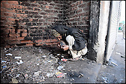 """A pathan man smokes heroin hid from the local people inside a broken building. Percentages of heroin and drug users are index of how many  people come from the NWFP. Morgh Mandi, Rawalpindi, Pakistan, on friday, November 28 2008.....""""Pakistan is one of the countries hardest hits by the narcotics abuse into the world, during the last years it is facing a dramatic crisis as it regards the heroin consumption. The Unodc (United Nations Office on Drugs and Crime) has reported a conspicuous decline in heroin production in Southeast Asia, while damage to a big expansion in Southwest Asia. Pakistan falls under the Golden Crescent, which is one of the two major illicit opium producing centres in Asia, situated in the mountain area at the borderline between Iran, Afghanistan and Pakistan itself. .During the last 20 years drug trafficking is flourishing in the Country. It is the key transit point for Afghan drugs, including heroin, opium, morphine, and hashish, bound for Western countries, the Arab states of the Persian Gulf and Africa..Hashish and heroin seem to be the preferred drugs prevalence among males in the age bracket of 15-45 years, women comprise only 3%. More then 5% of whole country's population (constituted by around 170 milion individuals),  are regular heroin users, this abuse is conspicuous as more of an urban phenomenon. The substance is usually smoked or the smoke is inhaled, while small number of injection cases have begun to emerge in some few areas..Statistics say, drug addicts have six years of education. Heroin has been identified as the drug predominantly responsible for creating unrest in the society."""""""