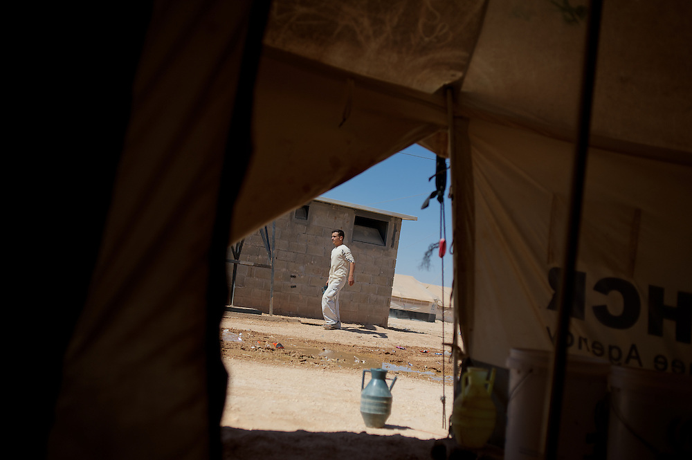 August 08, 2013 - Zaatari, Jordan: A syrian refugee passes by a communal toilet facility at Zaatari refugee camp in northern Jordan. Zaatari camp, home to more than 120,000 people who in the past year have fled the conflict in Syria, become the fourth largest city in Jordan and the world's second largest refugee camp behind Dadaab in eastern Kenya. Most of its residents came from Daraa, a city about 30Km away in Syria, rich with businessmen thanks to a long history of cross-border trade with Jordan. (Paulo Nunes dos Santos/Al Jazeera)