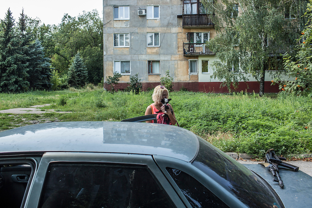 A resident of the Ploshchadka neighborhood, which has been heavily bombarded in recent days, awaits an escort from pro-Russia rebels to leave the neighborhood on Wednesday, July 30, 2014 in Donetsk, Ukraine.