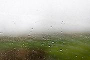 Rain runs along a window of train from Warsaw to Krakow, Poland