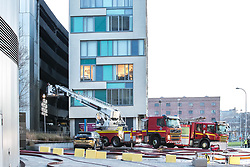 © Licensed to London News Pictures . 01/01/2018. Liverpool, UK. Charred exterior of the car park is visible in the left of the photograph with adjacent flats , which were evacuated, in the centre . Scene at the Liverpool Echo Arena car park where firefighters are working to extinguish a fire that started late on New Year's Eve and that destroyed all 1,400 cars parked in the multi-story car park. The Liverpool International Horse Show taking place at the Arena was abandoned and people and horses evacuated as dozens of fire crew worked to control the blaze . Photo credit: Joel Goodman/LNP