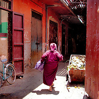 Woman in Djellaba Hurries from Market in Marrakech, Morocco <br /> Many of the streets and alleys of Marrakech are adorned by colorful doors, walls and windows reminiscent of a paint wheel from a hardware store. Equally colorful are women&rsquo;s robes such as this one called a djellaba or kaftan.  She seemed to be hurrying home with a package from the market.