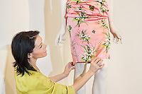 Beautiful mid adult woman adjusting dress on mannequin in fashion store