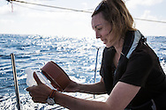 North Atlantic Ocean, September 2014.<br /> Marine biologist Stephanie Wright filters a sample recovered from a trawl through a mesh, on board the Sea Dragon. &copy; Chiara Marina Grioni