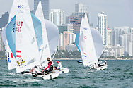 Miami, USA, February 1, 2014 - Unusually light conditions prevailed at he ISAF Sailing World Cup in Miami.  January usually brings cool temperatures and brisk breezes.  Pictured here:  the 470 men's fleet against the Miami skyline.