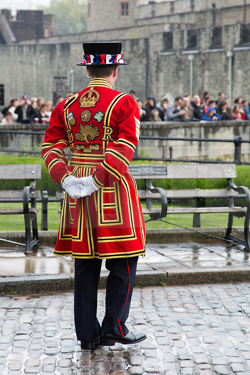 © Licensed to London News Pictures. 21/04/2014. London, UK. A Yeoman Warder watches the crowd as a 62 Gun Salute is fired by members of the Honourable Artillery Company (HAC) in honour of Her Majesty the Queen's 88th birthday today, 21st April 2014 at the Tower of London in front of Tower Bridge in London.. Photo credit : Vickie Flores/LNP