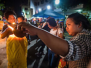 25 NOVEMBER 2015 - BANGKOK, THAILAND:  People light candles during Loy Krathong at Wat Yannawa in Bangkok. Loy Krathong takes place on the evening of the full moon of the 12th month in the traditional Thai lunar calendar. In the western calendar this usually falls in November. Loy means 'to float', while krathong refers to the usually lotus-shaped container which floats on the water. Traditional krathongs are made of the layers of the trunk of a banana tree or a spider lily plant. Now, many people use krathongs of baked bread which disintegrate in the water and feed the fish. A krathong is decorated with elaborately folded banana leaves, incense sticks, and a candle. A small coin is sometimes included as an offering to the river spirits. On the night of the full moon, Thais launch their krathong on a river, canal or a pond, making a wish as they do so.    PHOTO BY JACK KURTZ
