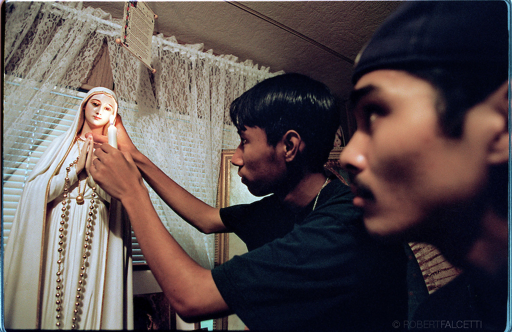 Pasco County, Fla.: Vimer Nagun uses a candle to show how the eyes dilate on a a statue of the Virgin Mary as one of his friends looks on. The photo was taken just several days after Nagun first claimed to have had apparitions of the Virgin Mary. In the first week, thousands of pilgrims arrived at the Nagun home.  (Photo by Robert Falcetti). .