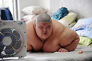 SHENYANG, CHINA - JULY 23: (CHINA OUT) <br /> <br /> Teenager who weighs 23 stone<br /> <br /> A 19-year-old boy, more than 150kg in weight, is seen at home on July 23, 2013 in Shenyang, Liaoning Province of China. As he is too fat, the boy can\'t move to the bathroom to take a shower by himself. His mother had to called the firefighters for help. <br /> ©Exclusivepix