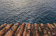 Detail of a terracotta roof and the blue water along the Amalfi Coast of Italy