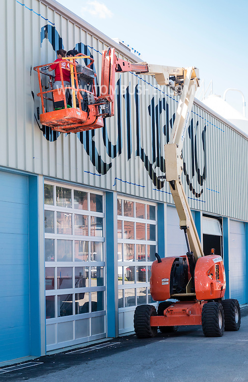 """Middletown, New York - Painters in a lift fill in the """"e"""" on the Equilibrium sign at Equilibrium Brewery on Aug. 23, 2016."""
