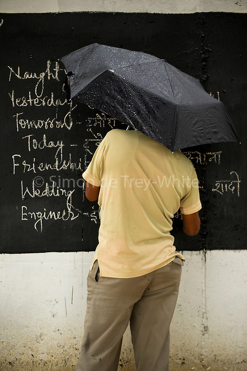 27th March 2014, Shakarpur, New Delhi, India.  Laxmi Chandra holding an umbrella writes during a rain shower on a freshly repainted blackboard on the walls of a metro bridge at a makeshift school under a metro bridge near the Yamuna Bank Metro station in Shakarpur, New Delhi, India on the 27th March 2014<br /> <br /> Rajesh Kumar Sharma (born 01/02/1970), started this makeshift school in 2011. Six mornings a week he teaches underprivileged children for three hours while his younger brother replaces him at his general store in Shakarpur. His students are children of labourers, rickshaw-pullers and farm workers. This is the 3rd site he has used to teach under privileged children in the city, he began in 1997. <br /> <br /> PHOTOGRAPH BY AND COPYRIGHT OF SIMON DE TREY-WHITE<br /> + 91 98103 99809<br /> email: simon@simondetreywhite.com<br /> photographer in delhi<br /> journalist
