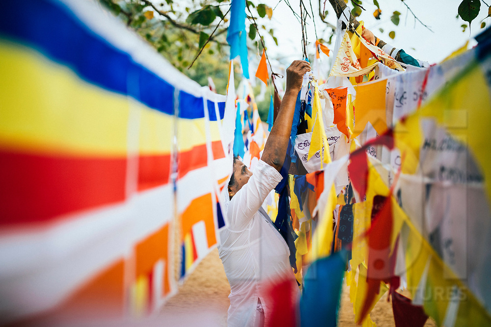 Woman hangs prayer flags in the Temple of the Tooth, Kandy, Sri Lanka, Asia