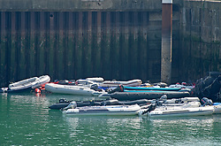 ©Licensed to London News Pictures 11/08/2020             Dover, UK. Migrant boats abandoned in a corner of Dover docks. Illegal migrants continue to cross the English Channel today from France, many are using inflatable dinghies with a motor on. Photo credit: Grant Falvey/LNP
