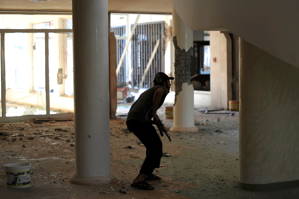 A rebel fighter takes cover during the attack to the Jewel Hotel in central Zawiya.