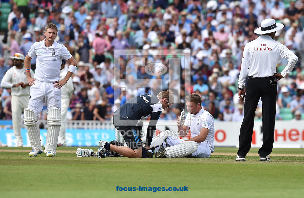 Batsman Jos Buttler of England gets some physic attention on his leg after being stuck by the ball during the Investec Test Match match at the Kia Oval, London<br /> Picture by Alan Stanford/Focus Images Ltd +44 7915 056117<br /> 16/08/2014