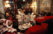 Costumed revelers in a café off the Piazza San Marco, during Winter Carnival in Venice, Italy.