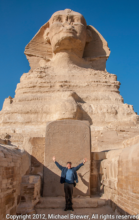 The photographer in front of the sphinx, giving perspective to the monumental size of the sculpture.  In Giza, Egypt.