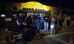 © Licensed to London News Pictures. 10/08/2011. LONDON, UK. Sikh males standing outside Gurdwara Sri Guru Singh Sabha, part of the largest Sikh temple in Europe, talk to one of their motorcycle riders recently back from patrolling the town in search of trouble. Organised, and coordinating with police, members of Southall's Sikh community come out in force to prevent any rioting from taking place in the area. The vigilante action took place as a fourth night of riots and looting were expected to take place in London. Photo credit: Matt Cetti-Roberts/LNP