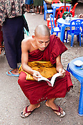 Monk reading at streetside book stall. Yangon, Myanmar.