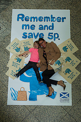 Environment minister Richard Lockhead launced a new public awareness campaign ahead of the introduction of a 5p charge for each single use carrier bag given to shoppers. Isaac Lee (aged 3) and his mother Susan got the message. Edinburgh,  25 September 2014 Ger Harley | StockPix.eu