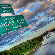 "Kansas City ""City Limits"" sign on Chouteau Trafficway Bridge over the Missouri River in the evening."