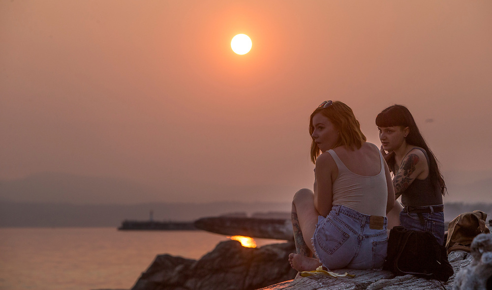 Two women take in the sunset at Holland Point Park below the Dallas Road Waterfront Trail in Victoria, British Columbia Canada on August 3, 2017. <br /> <br /> Smoke from wildfires in British Columbia&rsquo;s interior has drifted over Victoria and the lower mainland pushing air quality to a high risk level.