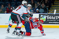 KELOWNA, CANADA -JANUARY 29: Kris Schmidli #16 and Ryan Olsen #27 of the Kelowna Rockets check Carter Proft LW #15 of the Spokane Chiefs to the ice during the second period on January 29, 2014 at Prospera Place in Kelowna, British Columbia, Canada.   (Photo by Marissa Baecker/Getty Images)  *** Local Caption *** Kris Schmidli; Ryan Olsen; Carter Proft;