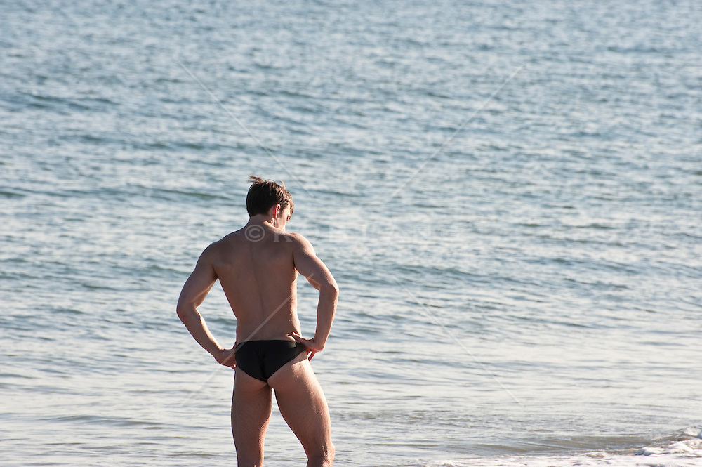 man in a speedo looking down standing on the beach with his hands on his hips