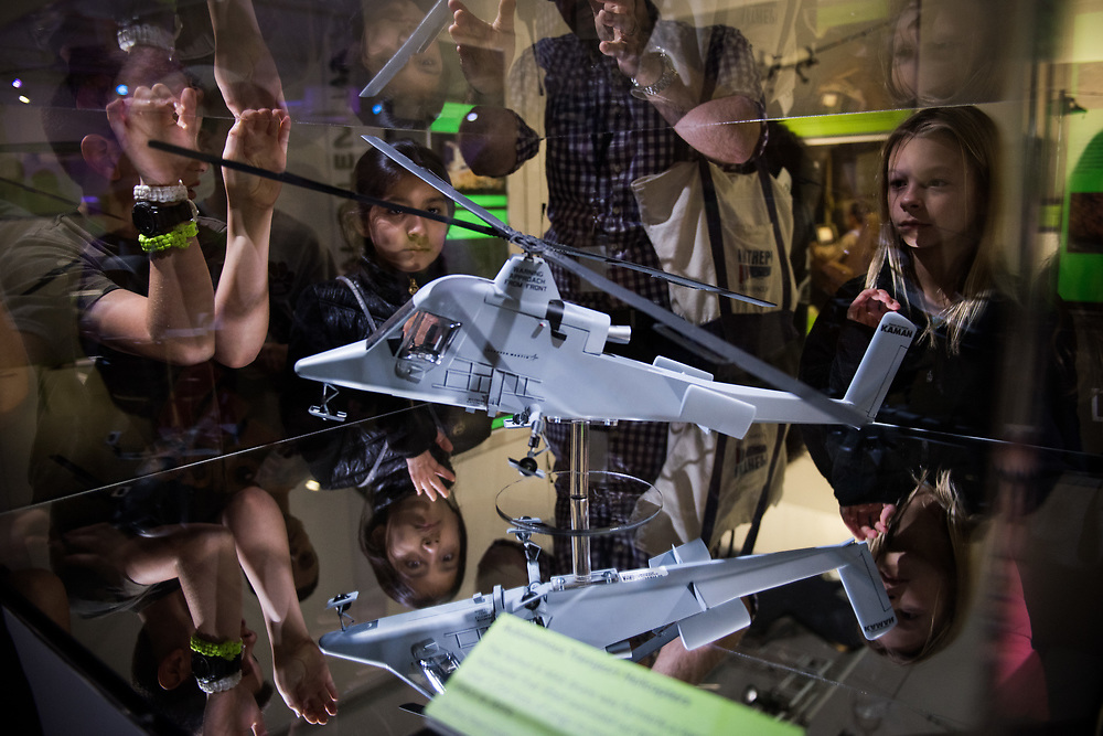 """30206010A - DRONES - Students from Kings Road School in Madison, NJ look at a model of the Kaman K-Max drone helicopter at the """"Drones: Is the Sky the Limit?"""" exhibit at the Intrepid Sea, Air, and Space Museum in New York, NY on May 9, 2017."""