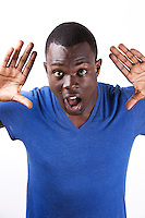 Portrait of shocked young man with palms open standing against white background