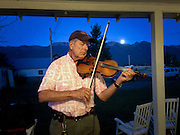 Paul Sebesta rehearsing playing his fiddle as the moonrises behind him