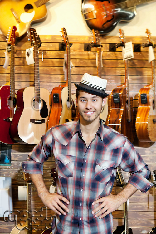 Portrait of a happy music store owner standing in front of guitars