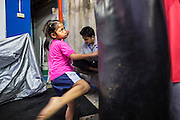 "18 DECEMBER 2104 - BANGKOK, THAILAND: A girl who wants to box works out by kicking a heavy bag at the Kanisorn gym. The Kanisorn boxing gym is a small gym along the Wong Wian Yai - Samut Sakhon train tracks. Young people from the nearby communities come to the gym to learn Thai boxing. Muay Thai (Muai Thai) is a Thai fighting sport that uses stand-up striking along with various clinching techniques. It is sometimes known as ""the art of eight limbs"" because it is characterized by the combined use of fists, elbows, knees, shins, being associated with a good physical preparation that makes a full-contact fighter very efficient. Muay Thai became widespread internationally in the twentieth century, when practitioners defeated notable practitioners of other martial arts. A professional league is governed by the World Muay Thai Council. Muay Thai is frequently seen as a way out of poverty for young Thais and Muay Thai camps and schools are frequently crowded. Muay Thai professionals and champions are often celebrities in Thailand.     PHOTO BY JACK KURTZ"
