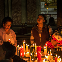 People pray at candlelight in front of an image of Jesus in one of the many churches in Quito, Ecuador.