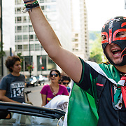 """Wearing a wrestler mask, a young mexican man protest in the street of Montreal against the """"fraudulent"""" election of Enrique Pena Nieto as the new mexican president."""