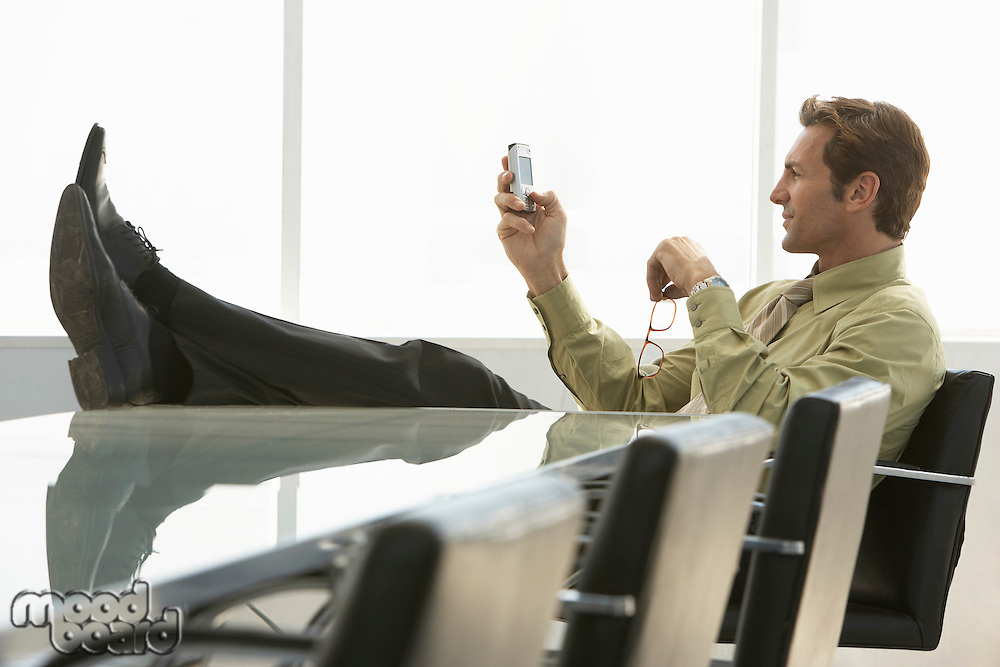Relaxed businessman with feet up text messaging on mobile phone in conference room