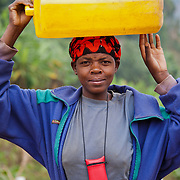 Uwamaliya Delphine, a Rwandan woman from Gatovu Community in Kisaro Sector, Rulindo District, Rwanda, carries a jerrycan of water from the local village tap on her head. Although it has abundant rainfall, Rwanda lacks sufficient storage, collection, catchment and/or distribution systems to supply water to its people, and thus many people spend hours each day hauling water from the local tap to their home.
