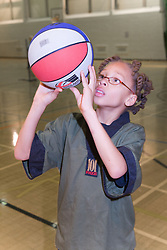 Young boy playing a game of basket ball in the sports hall of his local leisure centre,