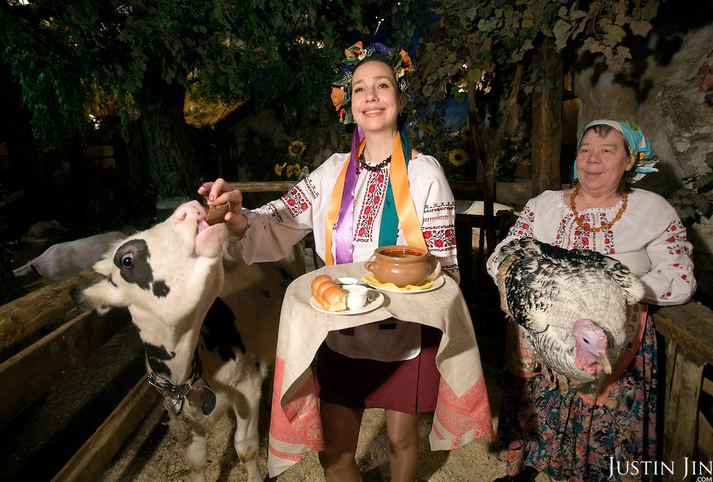 A waitress gives biscuit to a cow while holding a serving of borscht and bread at the Shinok restaurant in Moscow. Borsht is a traditional Ukrainian cuisine that has spreaded via Russia throughout the former Soviet sphere. Shinok is created by restaurateur Andrei Dellos, who made a barn with live animals inside the restaurant.