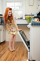 Full length of a young redheaded woman looking into an open oven
